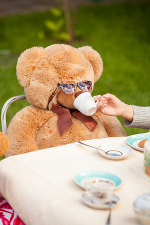 Closeup photo of girl giving tea to teddy bear in sunglasses photo