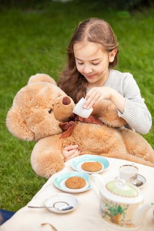Beautiful smiling girl giving tea to plush bear photo