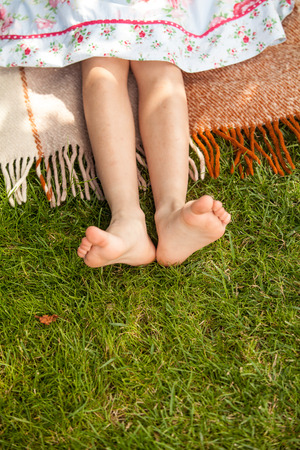 Closeup shot of small girls feet on grass at park photo