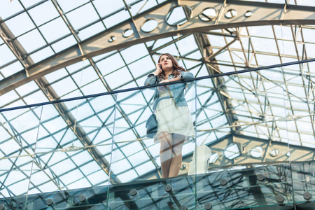 glass ceiling: Beautiful woman talking on cellphone at airport with glass ceiling