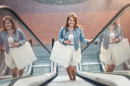 Happy shopping woman in shopping mall on escalator photo