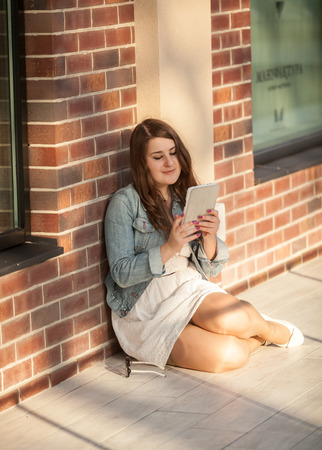 Closeup shot of young woman sitting on street and using tablet photo