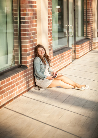 Beautiful woman sitting on street and leaning against brick wall photo