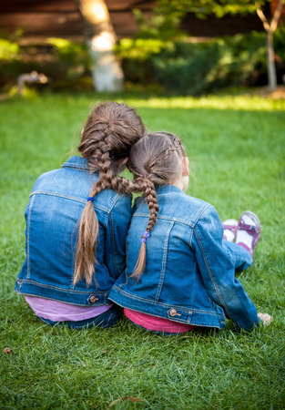 together with long tie: Two little sisters sitting on grass head to head with joint braids Stock Photo