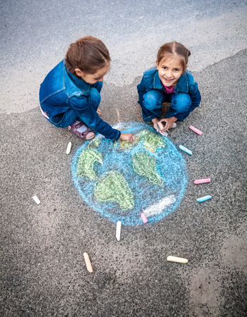 happy planet earth: Vista superior del tiro de dos ni�as de dibujo de la Tierra con tizas Foto de archivo