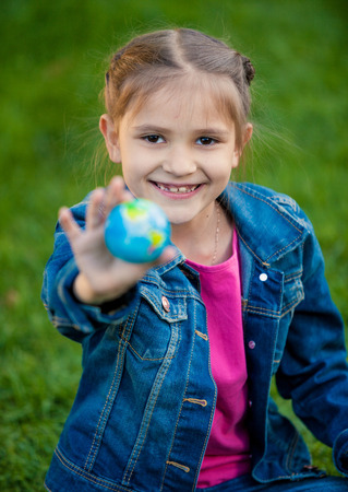 Closeup portrait of smiling girl holding globe in hand photo