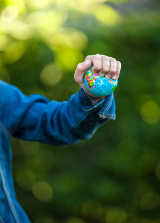 Closeup shot of little girl squeezing Earth globe at hand Stock Photo