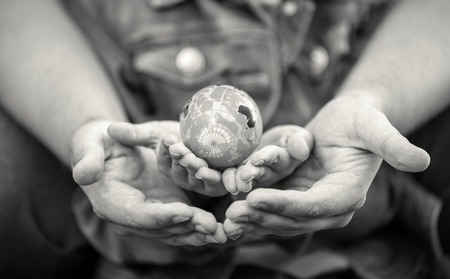 Black and white shot of man protecting girls hands holding globe Stock Photo