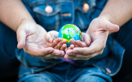 Closeup photo of man holding girls hands with earth globe photo