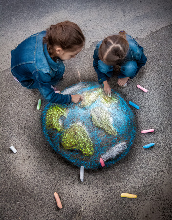 Top view shot of two girls drawing realistic Earth image with chalks on ground