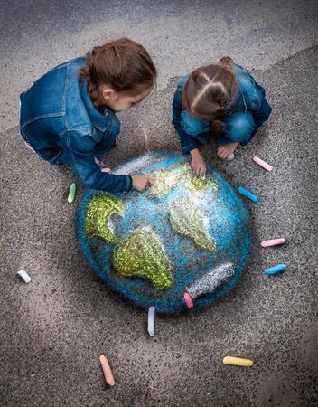 planeta tierra feliz: Vista superior del tiro de dos niñas Tierra imagen realista de dibujo con tizas en terreno