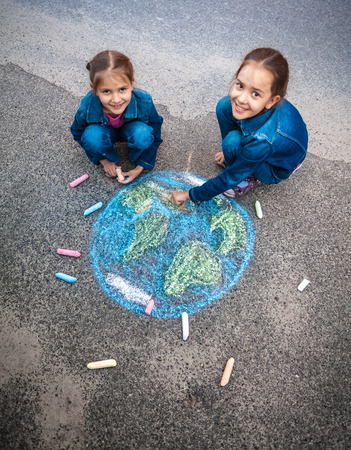 Two smiling girls drawing Earth with chalks on street Stock Photo