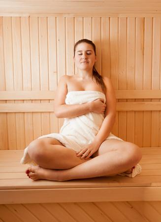 sauna nackt: Sch�ne nackte Frau liegt entspannt auf der Bank an der Sauna