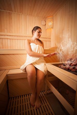 sauna nackt: Foto der schönen Frau sitzt neben bei Saunaofen Lizenzfreie Bilder