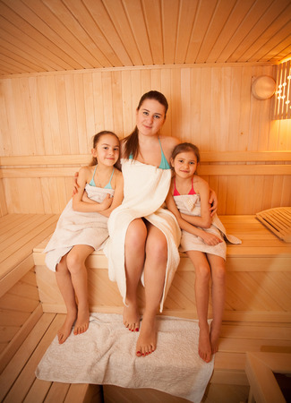 Portrait of woman with little girls relaxing at finnish sauna photo