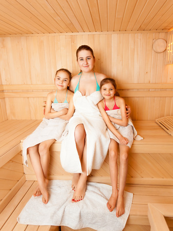 Positive mother with daughters relaxing at steam bath photo