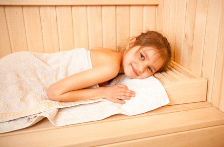 little girl bath: Closeup portrait of little girl lying on towel at sauna Stock Photo
