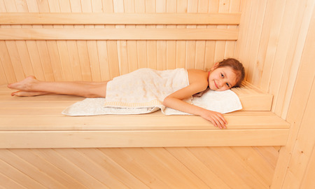 woman bath: Portrait of cute little girl relaxing on bench at sauna