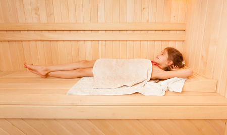 steam room: Cute little girl covered in towel lying at steam bath