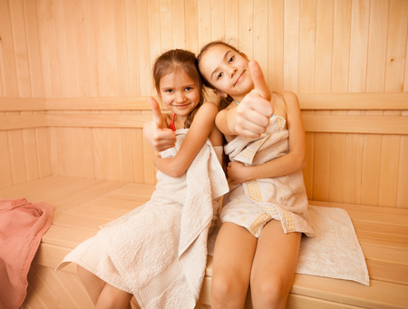 finnish bath: Two happy little girls in sauna showing thumbs up
