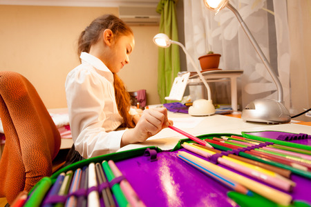 Wide angle portrait of little girl taking pencil of pencil-case photo