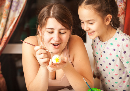 Closeup portrait of mother and girl painting easter eggs photo
