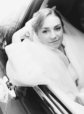 Black and white portrait of beautiful bride looking out of car photo