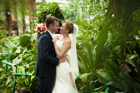 Portrait of newly married couple kissing at forest photo