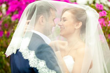 recien casados: Primer retrato de pareja de recién casados ??bajo el velo blanco Foto de archivo