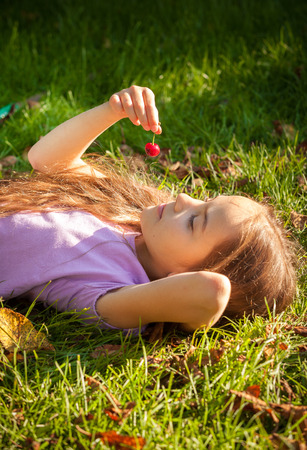 Portrait of little girl lying on grass and looking at red cherry photo