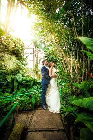 Full length portrait of bride and groom hugging under bamboo at jungle photo