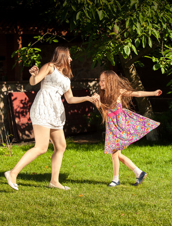 Beautiful brunette woman an young girl holding ands and dancing at yard photo
