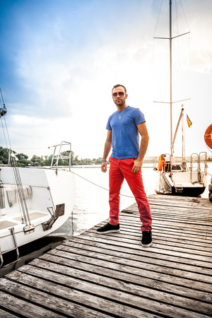 Full length portrait of handsome man standing on pier against white yachts photo