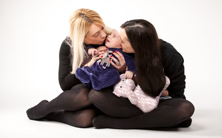 lithe: Young mother and sister kissing lithe baby on floor at studio