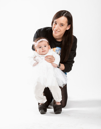 Studio portrait of young mother holding little daughter in high heel shoes photo