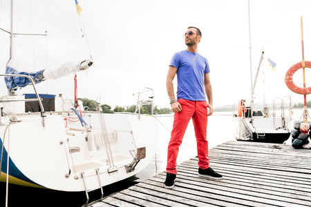 Handsome macho man posing at seaport against yachts photo
