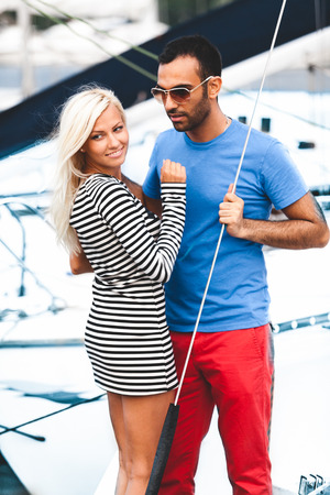 Handsome latin man hugging sexy blonde woman on yacht photo