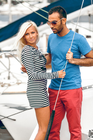 Portrait of handsome latin man and blond woman standing on yacht photo