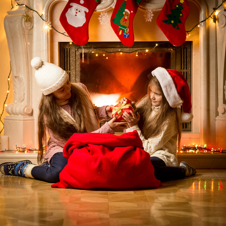 one room school house: Portrait of two little girls having a fight of present on Christmas Stock Photo
