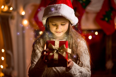 christmas fireplace: Little cute girl looking inside of glowing Christmas present box