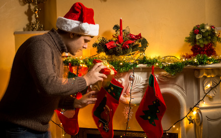 Portrait of young father putting gifts in Christmas stockings at fireplace photo