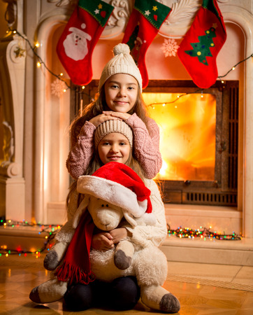 baby open present: Portrait against fireplace of smiling girls sitting on floor with toy sheep