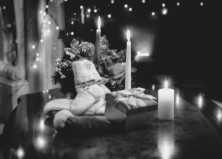 Black and white photo of table decorated with christmas candles, gifts and socks photo