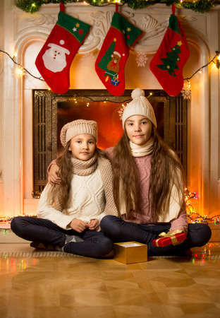 Portrait of two cute girls sitting next to decorated fireplace for Christmas photo