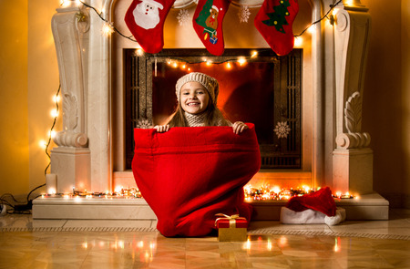 babies laughing: Little girl sitting in big red sack at room decorated for Christmas