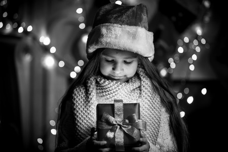 Black and white portrait of smiling girl opening Christmas present box photo
