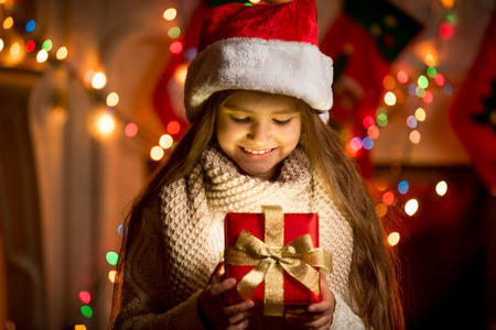 Portrait of little girl looking at open box with Christmas present