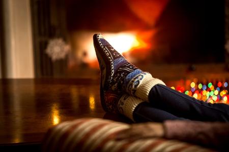 camino natale: Ritratto del primo piano dei piedi in calzini di lana che scaldano al camino in inverno