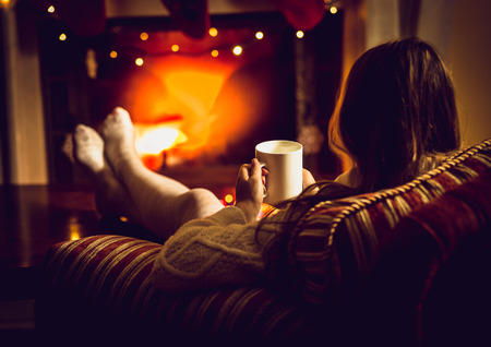 Toned photo of woman warming up with hot tea at fireplace at winter Stock Photo