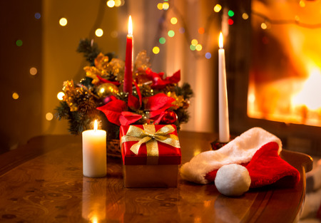 Beautiful christmas photo of burning candles with giftbox against fireplace photo